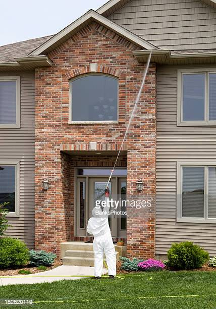 Pest Control Worker Spraying the Entry of a 2-Story Home