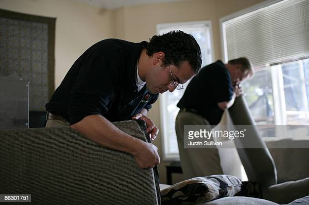 Pestec technicians Carlos I Agurto and Darrell Azlin inspect couch cushions for bed bugs at an apartment with bed bugs April 30 2009 in San Francisco...