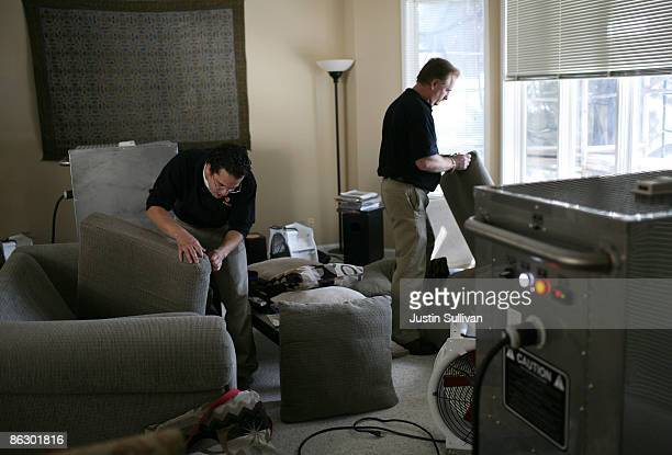 Pestec technicians Carlos I Agurto and Darrell Azlin inspect couch cushions as they prepare to heat treat an apartment with bed bugs April 30 2009 in...