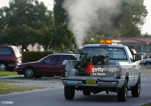 Pesticide spews from the fogger on the back of a MiamiDade Mosquito Control truck driven by David Anderson as he sprays for the insect in a...