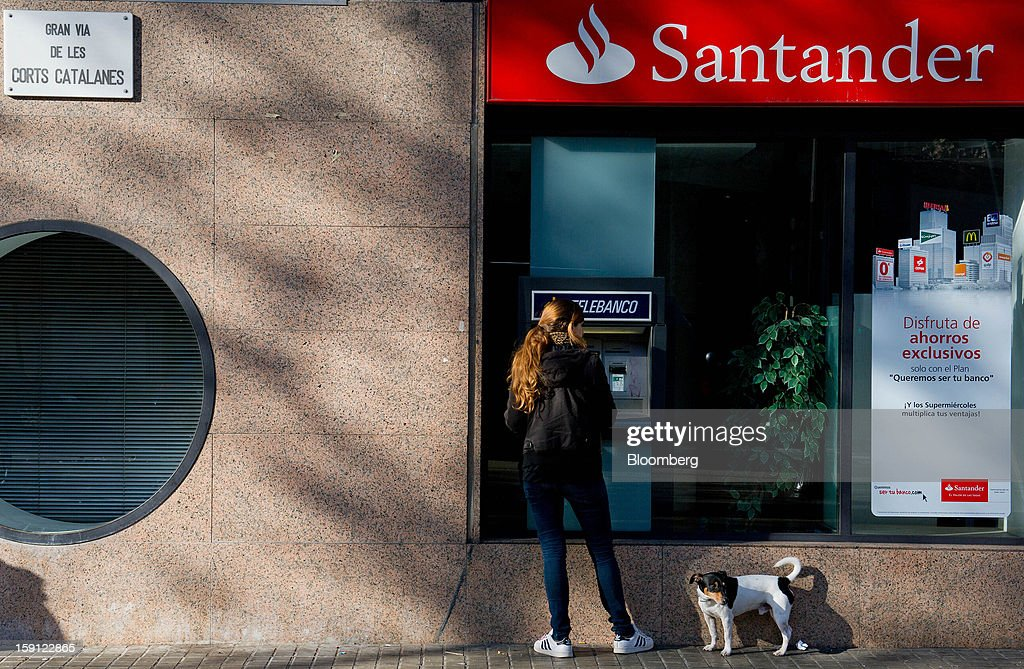 A pet dog stands beside a customer using an automated teller machine (ATM) outside a Banco Santander SA bank branch in Barcelona, Spain, on Tuesday, Jan. 8, 2013. Banco Santander SA, Spain's biggest lender, will offer 263 million euros ($345 million) in stock to buy out minority investors in its Banco Espanol de Credito SA retail unit and close 700 local branches to cut costs. Photographer: David Ramos/Bloomberg via Getty Images