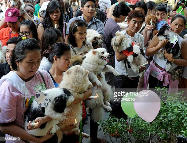 Pet owners queue to have a Catholic priest bless their pet dogs and cats during an event in Manila on March 17 2013 A local government is offering...