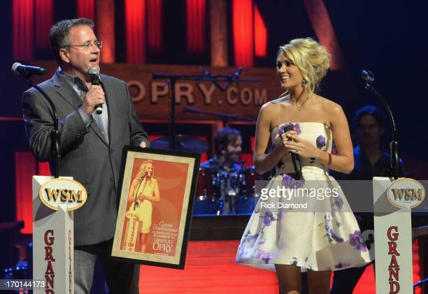 Pete Fisher General Manager of the Grand Ole Opry presents a Hatch Show Print to Carrie Underwood onstage in celebration of her 5th anniversary at...