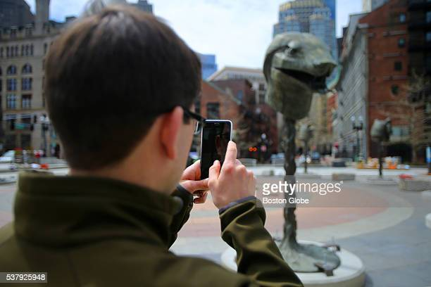 Pete Hanley of Boston takes a cell phone picture of the snake head as workers from More Specialized Transport of New Jersey install artist Ai...