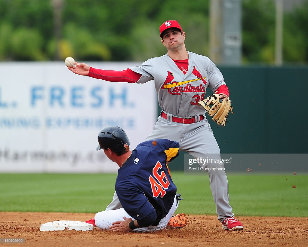Pete Kozma #38 of the St. Louis Cardinals turns a double play against Rick Ankiel #46 of the Houston Astros a spring training game at Osceola County Stadium on March 1, 2013 in Kissimmee, Florida.