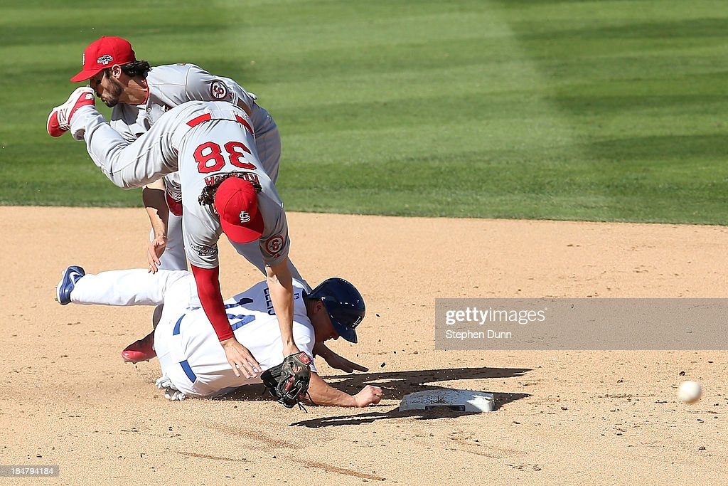 <a gi-track='captionPersonalityLinkClicked' href=/galleries/search?phrase=Pete+Kozma&family=editorial&specificpeople=6800748 ng-click='$event.stopPropagation()'>Pete Kozma</a> #38 of the St. Louis Cardinals turns a double play alongside teammate Matt Carpenter #13 as <a gi-track='captionPersonalityLinkClicked' href=/galleries/search?phrase=Mark+Ellis+-+Baseball+Player&family=editorial&specificpeople=213759 ng-click='$event.stopPropagation()'>Mark Ellis</a> #14 of the Los Angeles Dodgers attempts to break it up in the third inning in Game Five of the National League Championship Series at Dodger Stadium on October 16, 2013 in Los Angeles, California.