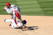 Pete Kozma of the St Louis Cardinals turns a double play alongside teammate Matt Carpenter as Mark Ellis of the Los Angeles Dodgers attempts to break...