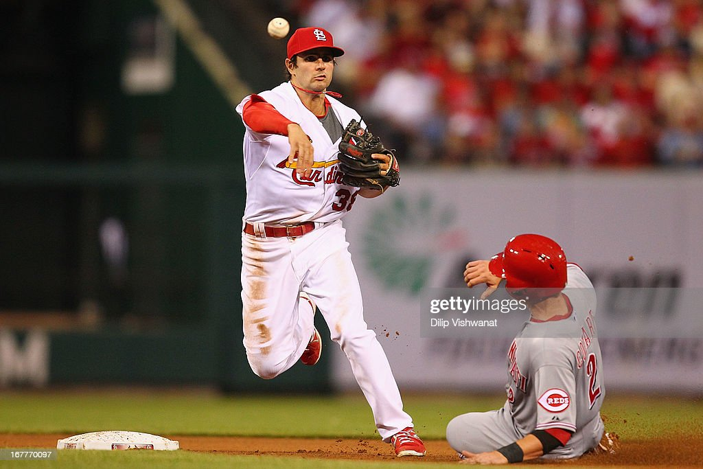 Pete Kozma #38 of the St. Louis Cardinals turns a double play over Zack Cozart #2 of the Cincinnati Reds in the second inning at Busch Stadium on April 29, 2013 in St. Louis, Missouri.
