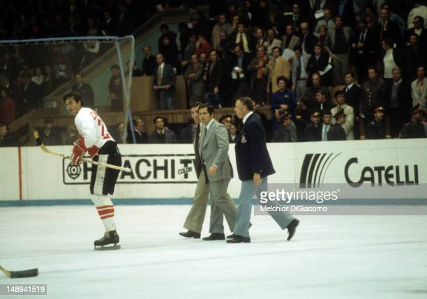Pete Mahovlich of Canada skates off the ice in front of head coach Harry Sinden and assistant coach John Ferguson during the 1972 Summit Series...