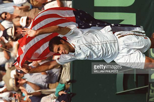 Pete Sampras of the US carries a US flag around the court of the Fitzgerald Tennis Center in Washington 21 September celebrating his defeat of...
