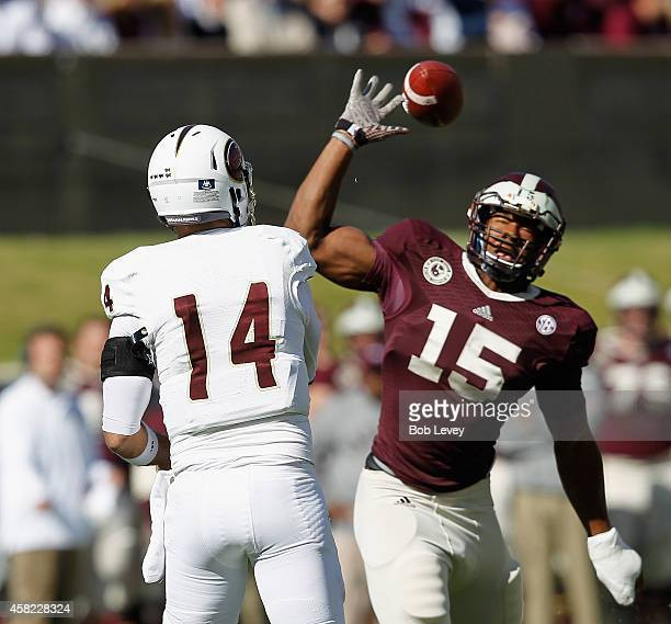 Pete Thomas of the Louisiana Monroe Warhawks throws over Myles Garrett of the Texas AM Aggies at Kyle Field on November 1 2014 in College Station...