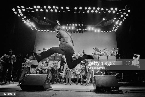 Pete Townshend of The Who leaps across the front of the stage while performing with an all star band headed by Paul McCartney and including members...