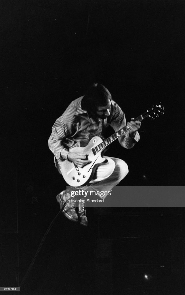 Pete Townshend, songwriter and guitarist of the British rock band The Who, seen in flight, whilst playing with the band on stage in 1975.