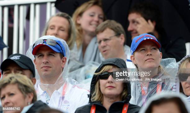 Peter and Autumn Phillips wear ponchos as the rain falls during the Individual Eventing Jumping Final on day four of the London Olympic Games at...