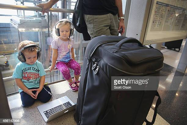 Peter and Elana Vlahos watch a movie while their parents try to reschedule a flight to Los Angeles at O'Hare International Airport on September 26...