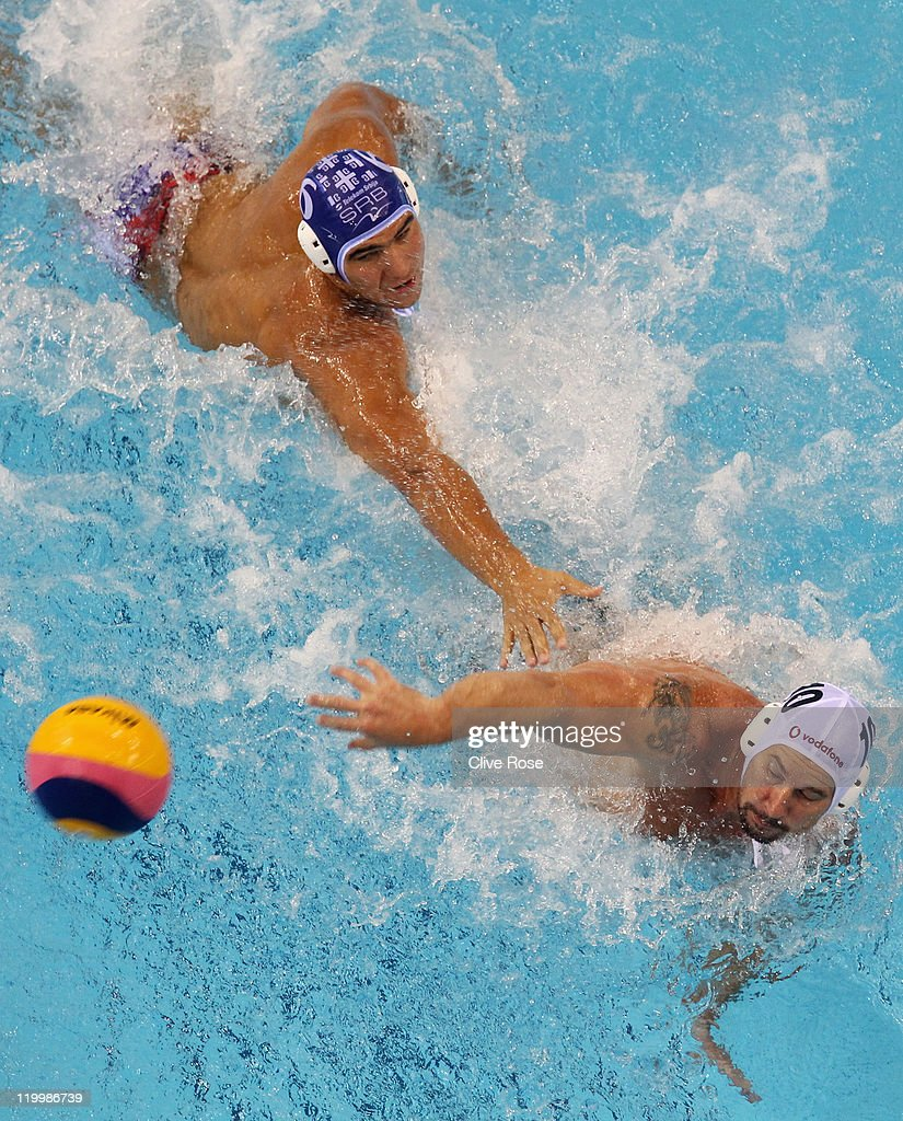 Peter Biros of Hungary and Dusko Pijetlovic of Serbia stretch for the ball in the Men's Water Polo semi final match between Hungary and Serbia during Day Thirteen of the 14th FINA World Championships at the Oriental Sports Center on July 28, 2011 in Shanghai, China.