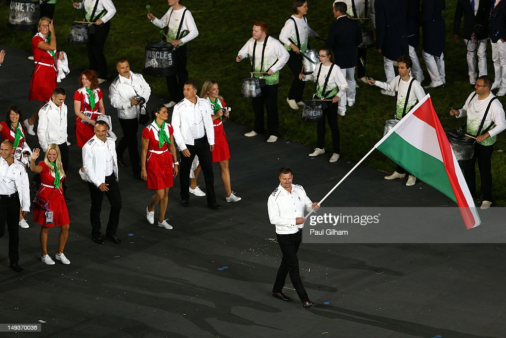 Peter Biros of the Hungary Olympic water polo team carries his country's flag during the Opening Ceremony of the London 2012 Olympic Games at the Olympic Stadium on July 27, 2012 in London, England.