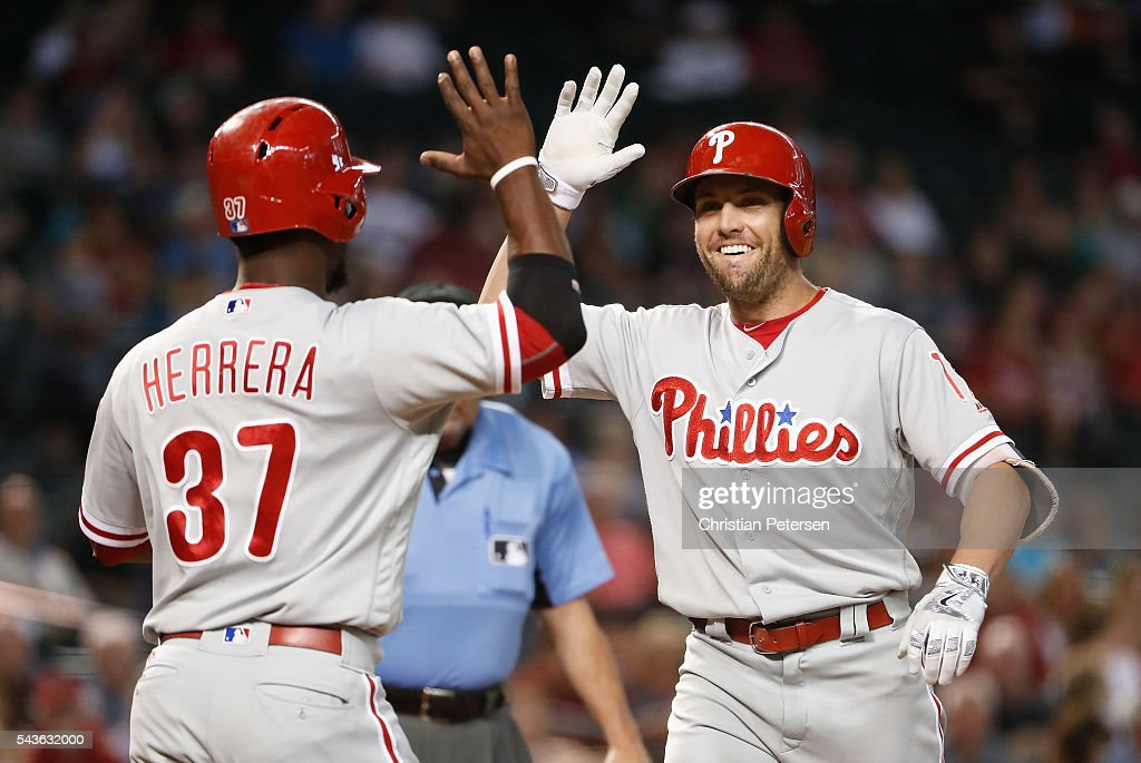 <a gi-track='captionPersonalityLinkClicked' href=/galleries/search?phrase=Peter+Bourjos&family=editorial&specificpeople=4959085 ng-click='$event.stopPropagation()'>Peter Bourjos</a> #17 of the Philadelphia Phillies high-fives <a gi-track='captionPersonalityLinkClicked' href=/galleries/search?phrase=Odubel+Herrera&family=editorial&specificpeople=13795312 ng-click='$event.stopPropagation()'>Odubel Herrera</a> #37 after Bourjos hit a two-run home run against the Arizona Diamondbacks during the first inning of the MLB game at Chase Field on June 29, 2016 in Phoenix, Arizona.