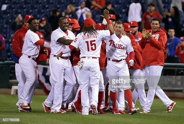 Peter Bourjos of the Philadelphia Phillies is mobbed by teammates after hitting a game winning walkoff infield single in the 11th inning during a...