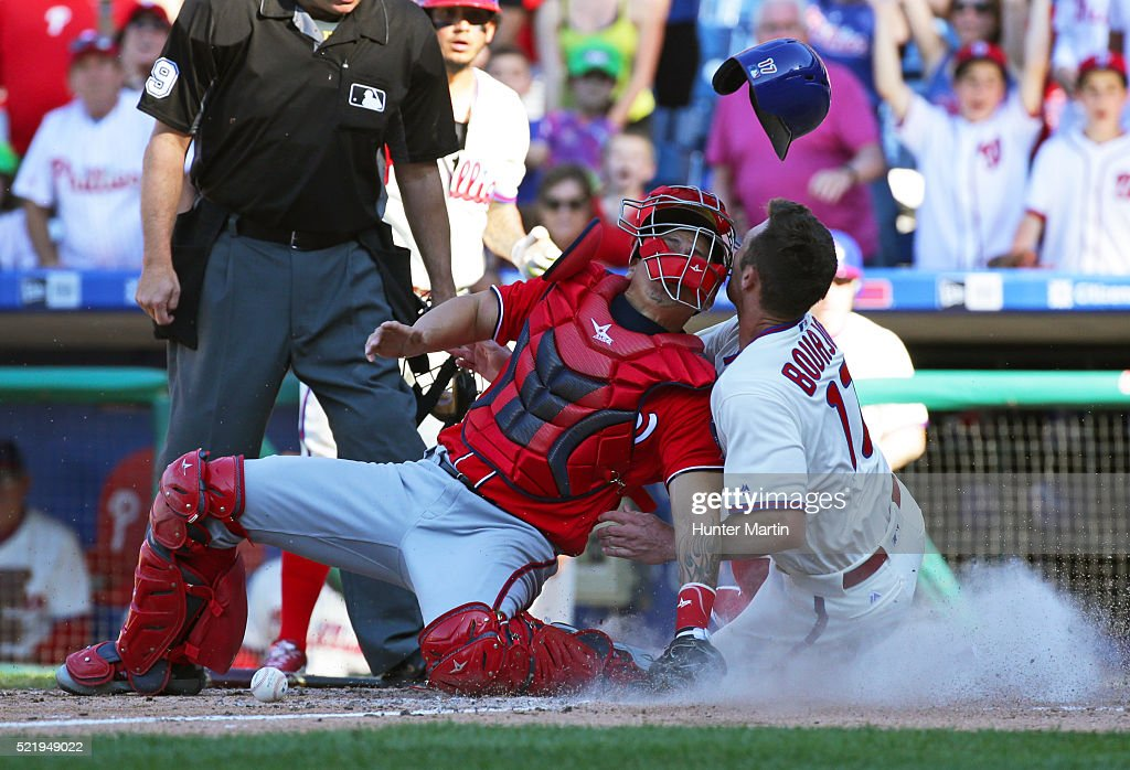 Peter Bourjos #17 of the Philadelphia Phillies scores the game tying run as he collides with Jose Lobaton #59 of the Washington Nationals in the tenth inning during a game at Citizens Bank Park on April 17, 2016 in Philadelphia, Pennsylvania. The Phillies won 3-2 in ten innings.