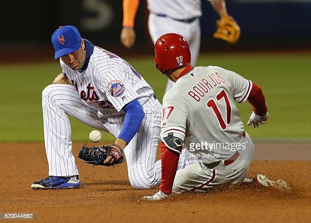 Peter Bourjos of the Philadelphia Phillies slides into second base with a double as second baseman Neil Walker of the New York Mets can't make a...