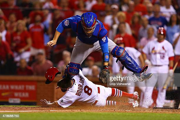 Peter Bourjos of the St Louis Cardinals scores the gamewinning run against Miguel Montero of the Chicago Cubs on a throwing error in the tenth inning...