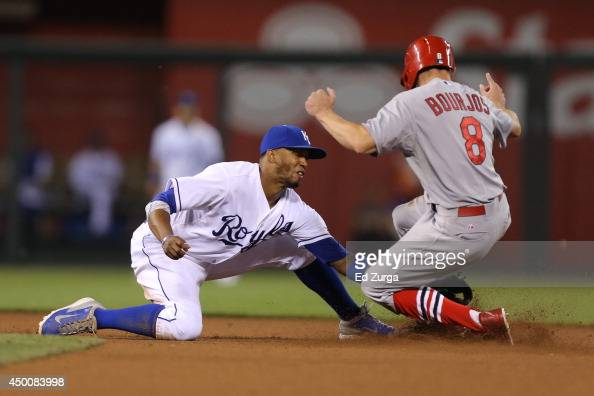 Peter Bourjos of the St Louis Cardinals slides into second base for a steal ahead of the tag of Alcides Escobar of the Kansas City Royals in the 11th...