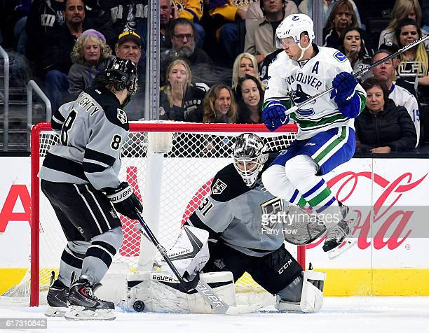 Peter Budaj of the Los Angeles Kings makes a save as Daniel Sedin of the Vancouver Canucks jumps out of the way in front of Drew Doughty during the...