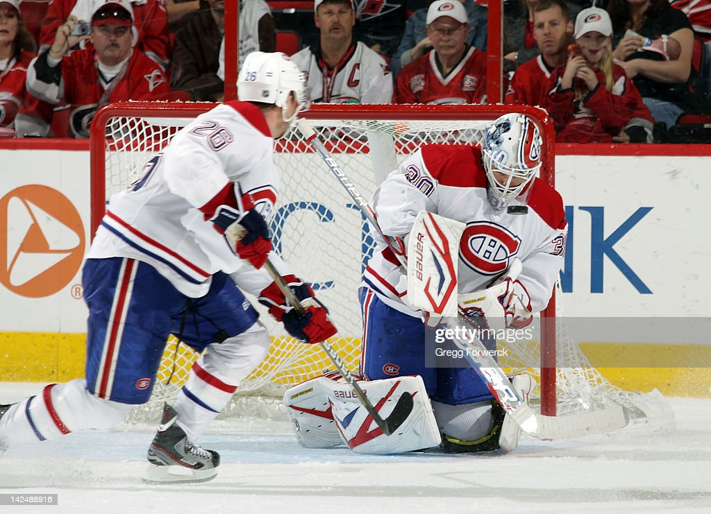 <a gi-track='captionPersonalityLinkClicked' href=/galleries/search?phrase=Peter+Budaj&family=editorial&specificpeople=228123 ng-click='$event.stopPropagation()'>Peter Budaj</a> #30 of the Montreal Canadiens bodies down the puck as <a gi-track='captionPersonalityLinkClicked' href=/galleries/search?phrase=Josh+Gorges&family=editorial&specificpeople=550446 ng-click='$event.stopPropagation()'>Josh Gorges</a> #26 prepares for a rebound during an NHL game on Apri 5, 2012 at PNC Arena in Raleigh, North Carolina.