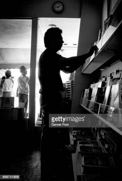 Peter Buena a sales clerk for B Dalton bookstore 16th street mall attempts to do his afternoon sorting and stocking of magazines under dim window...