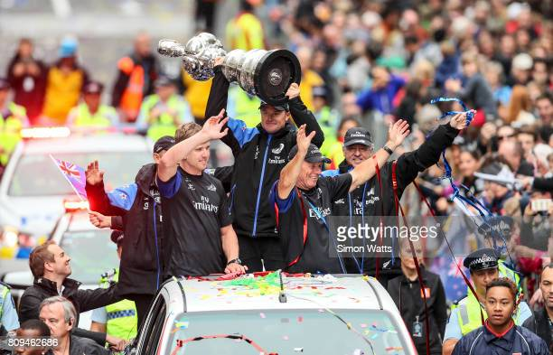 Peter Burling and Grant Dalton celebrate as Glenn Ashby holds the Americas Cup during the Team New Zealand Americas Cup Welcome Home Parade on July 6...