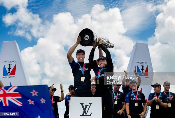 Peter Burling Helmsman and Glenn Ashby skipper of Emirates Team New Zealand lift the America's Cup trophy as Emirates Team New Zealand win race 9...