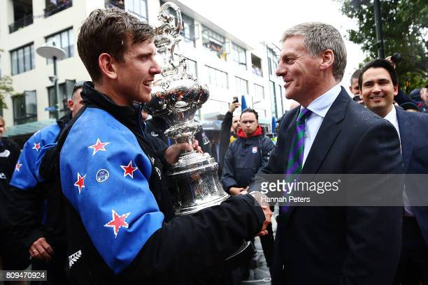 Peter Burling of Team New Zealand holds up the Americas Cup and is congratulated by New Zealand Prime Minister Bill English during the Team New...