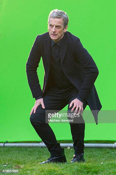 Peter Capaldi crouches in front of a large green screen during filming for the eighth series of BBC show Doctor Who in Bute Park on March 18 2014 in...