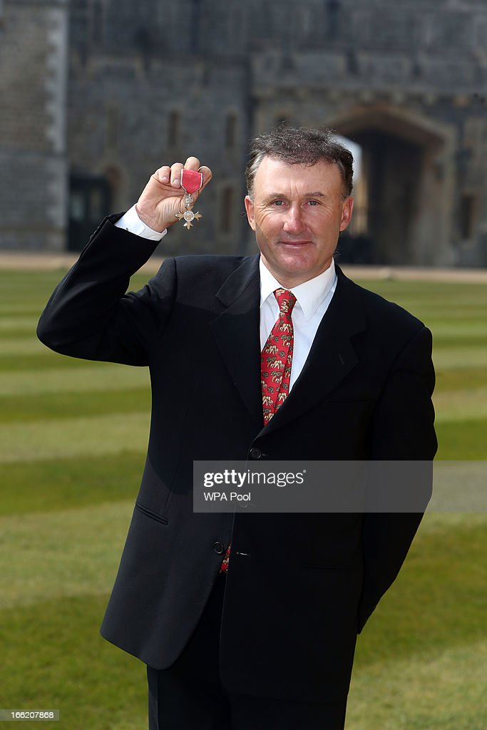 Peter Charles poses with his MBE after an Investiture ceremony at Windsor Castle on April 10, 2013 in Windsor, England.