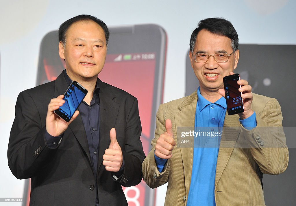 Peter Chou (L) and Chunghwa Telecom chairman and CEO Shyue-Ching Lu (R) display the new smartphone 'HTCJ butterfly' during a press conference in Taipei on December 11, 2012. The new smartphone has a quad-core CPU, 5-inch sized high-definition LCD display and an 8 mega-pixel CMOS camera. AFP PHOTO / Mandy CHENG