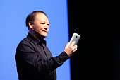 Peter Chou chief executive officer of HTC Corp holds an HTC M9 smartphone device during a news conference ahead of the Mobile World Congress 2015 in...
