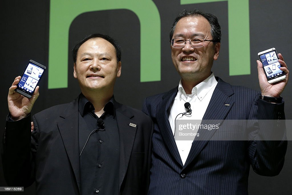 Peter Chou chief executive officer of HTC Corp left and Takashi Tanaka president of KDDI Corp hold the company's HTC J One HTL22 smartphones for KDDI...
