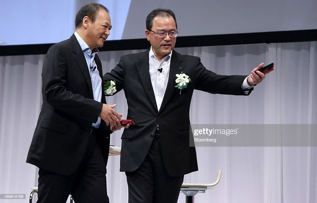Peter Chou chief executive officer of HTC Corp left is escorted by Takashi Tanaka president of KDDI Corp during the unveiling of the HTC J butterfly...