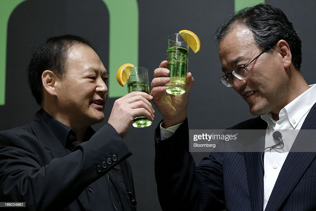 Peter Chou chief executive officer of HTC Corp left makes a toast with Takashi Tanaka president of KDDI Corp at the unveiling event for the HTC J One...
