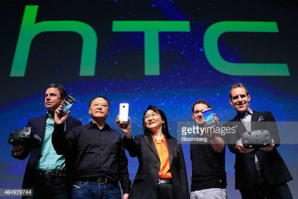 Peter Chou chief executive officer of HTC Corp second left and Cher Wang cofounder and chairperson of HTC Corp center hold up the new M9 smartphone...