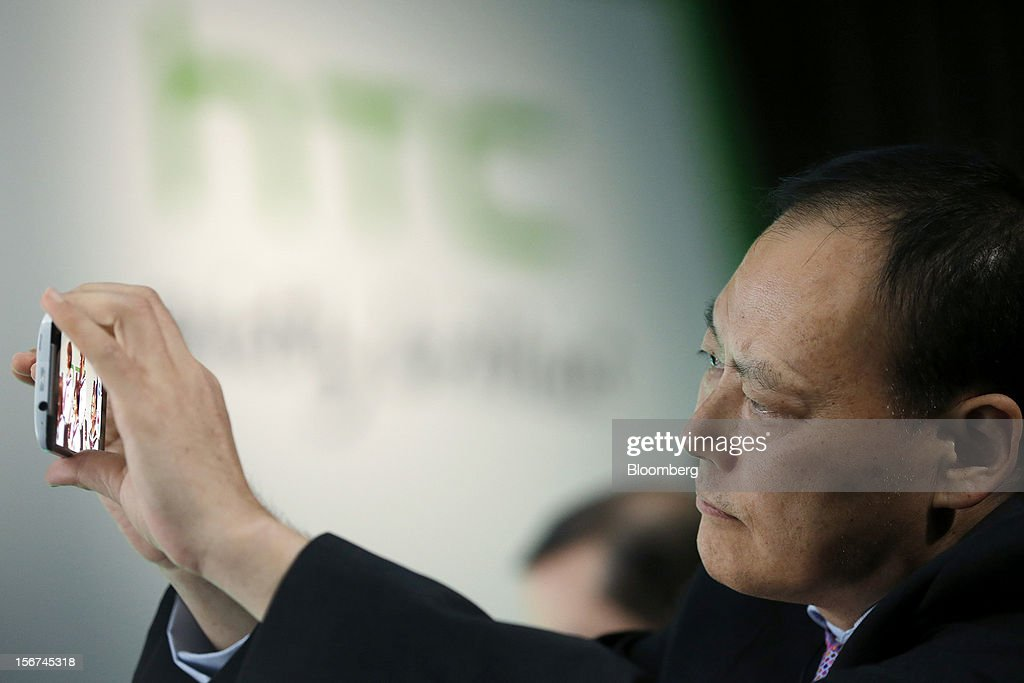 Peter Chou, chief executive officer of HTC Corp., uses the new HTC J Butterfly smartphone during the unveiling event in Tokyo, Japan, on Tuesday, Nov. 20, 2012. Taiwan's HTC Corp. needs to improve its global brand awareness to gain share in China, and its newly unveiled model is likely to help the vendor do that. Photographer: Kiyoshi Ota/Bloomberg via Getty Images