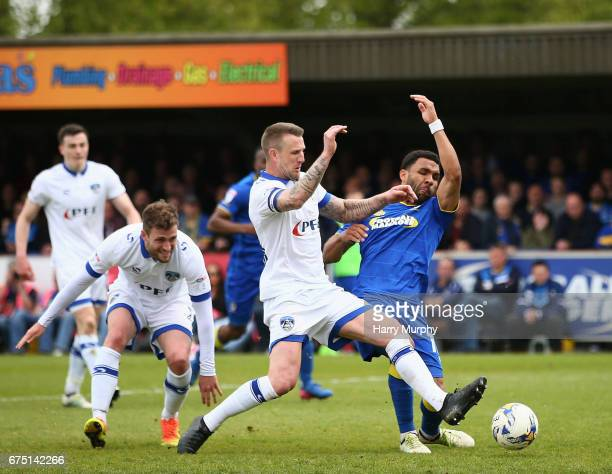Peter Clarke of Oldham Athletic and Andy Barcham of AFC Wimbledon challenge for the ball during the Sky Bet League One match between AFC Wimbledon...