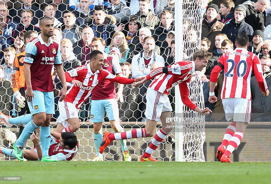 Peter Crouch (2R) and Peter Odemwingie (4R) of Stoke City celebrate as Crouch's shot deflects into the goal off of Odemwingie for their first goal during the Barclays Premier League match between Stoke City and West Ham United at Britannia Stadium on March 15, 2014 in Stoke on Trent, England.
