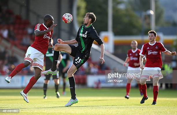 Peter Crouch of Stoke City battles with Manny Smith of Wrexham during the pre season friendly match between Wrexham and Stoke City at Racecourse...