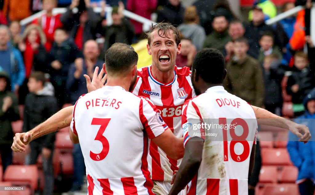 Peter Crouch (C) of Stoke City celebrates scoring his sides second goal with his team mates Erik Pieters (L) and Mame Biram Diouf (R) during the Premier League match between Stoke City and Southampton at Bet365 Stadium on September 30, 2017 in Stoke on Trent, England.