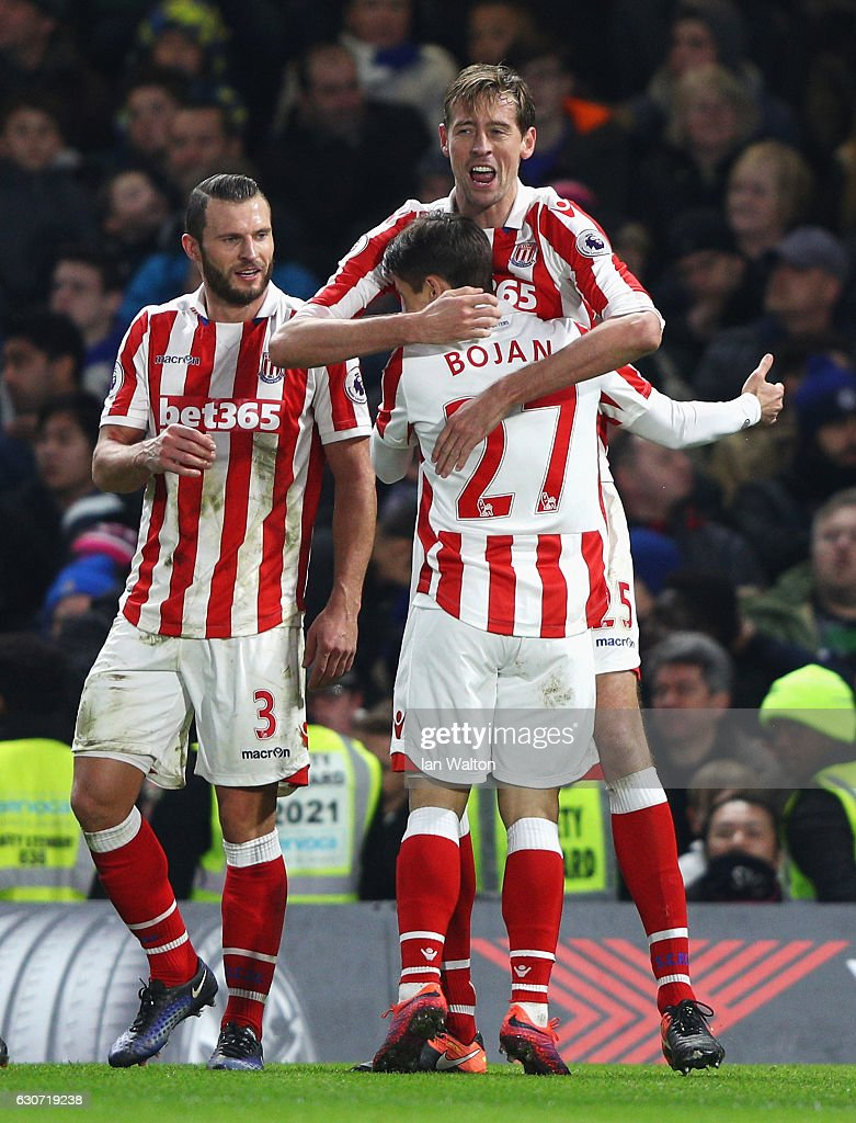 Peter Crouch (C) of Stoke City celebrates scoring his team's second goal with his team mates Bojan Krkic (R) and Erik Pieters (L) during the Premier League match between Chelsea and Stoke City at Stamford Bridge on December 31, 2016 in London, England.