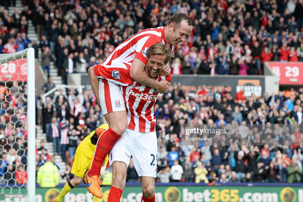 Peter Crouch of Stoke City celebrates scoring his team's sixth goal with his team mate Charlie Adam during the Barclays Premier League match between Stoke City and Liverpool at Britannia Stadium on May 24, 2015 in Stoke on Trent, England.