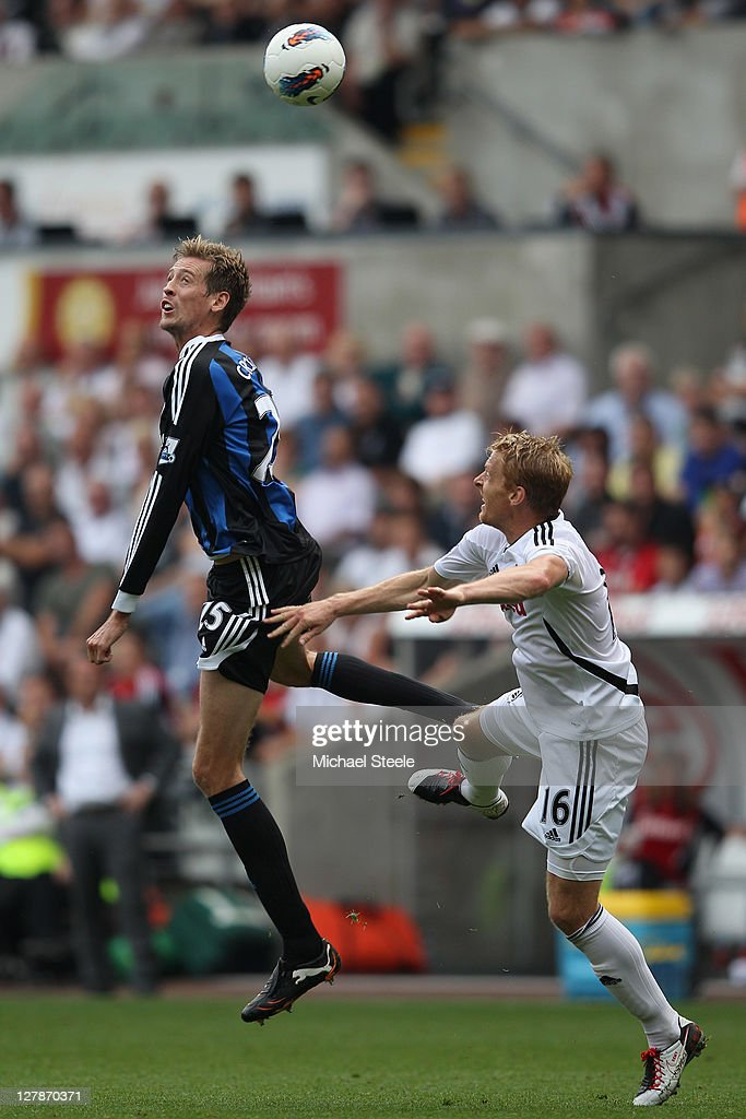 Peter Crouch (L) of Stoke City jumps above Garry Monk (R) of Swansea City during the Barclays Premier League match between Swansea City and Stoke City at the Liberty Stadium on October 2, 2011 in Swansea, Wales.
