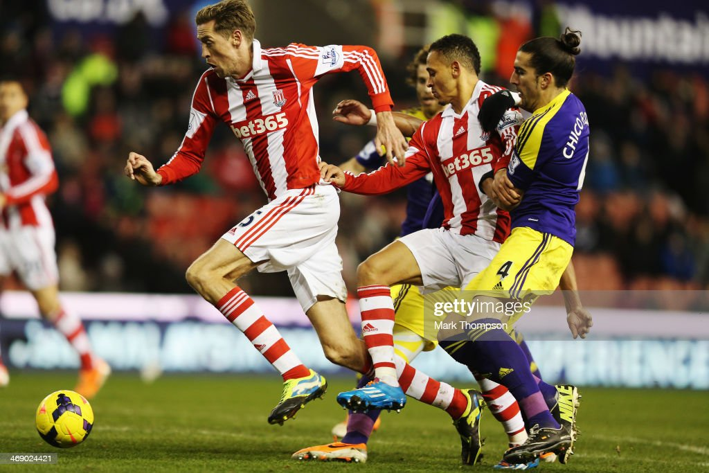 Peter Crouch of Stoke City tries to evade the tackle of Chico Flores of Swansea City during the Barclays Premier League match between Stoke City and...